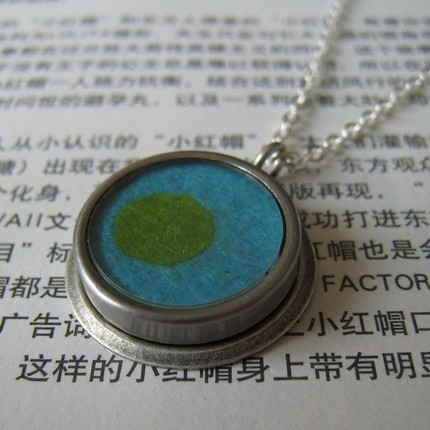 Necklace with felted pendant in turquoise with a green polkadot